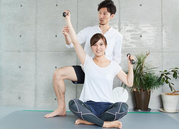 上腕三頭筋をダンベルで鍛えている女性と男性トレーナーの画像