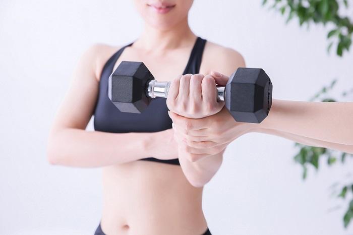 ダンベルを使って上腕三頭筋を鍛えている女性の画像